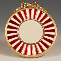 A Faberge two-color gilded silver and enamel photograph frame, workmaster Michael Perchin, St Petersburg, circa 1899-1903, scratched inventory number 5182. Circular in form, the frame surmounted with a gilded silver bow knot and enameled with alternating panels of translucent red and opaque white enamel over an engine-turned ground, the aperture framed in seed pearls. John Atzbach.