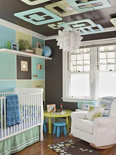 Baby Gone Mod - Avoiding babyish pastels and choosing bright, stimulating colors creates an unthemed place that can change as the tiny resident grows into his or her own interests. An easy-to-replicate colorful grid wall like this sets off the overhead plywood art hung from the ceiling.