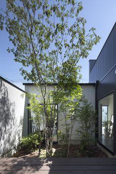 CASE 337 | アトリエのある家 白い塗り壁と黒い金属サイディングを使いコントラストをつけたファサード。アトリエ・玄関・LDKが中庭を介してつながっており、光と植栽の緑をそれぞれの空間に注ぎ込みます。多趣味のご主人は、アトリエをご自分の作業場や作品を展示するギャラリーとして使用するため、天井を高くして南側からたくさんの光を取り入れて気持ちのいい空間になっています。 設計監理:フリーダムアーキテクツデザイン 施工場所:奈良県橿原市