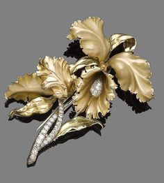 A diamond-set brooch  Realistically designed as a flower, the pistil and stem set with brilliant-cut diamonds, to textured leaves, diamonds approx. 1.00ct total, length 8.3cm