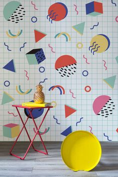 Take on the Memphis movement with these punchy wallpaper designs. Dazzlingly bright and funky shapes appear to float against a linear grid. Pair with abstract furniture and vivid colours to complete the look.