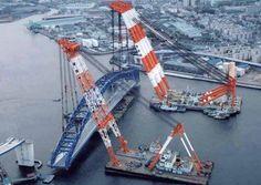 Twin floating barge cranes setting a bridge span.