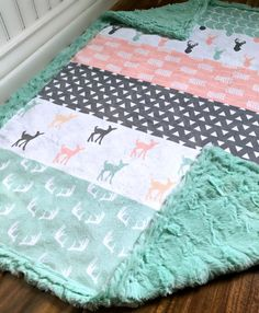This baby blanket has minky on both sides. The front side is one solid piece of designer minky. It has strips of fawns, triangles, arrows, antlers and deer heads in mint grey and blush (the top is one solid piece of minky that has not been cut or quilted). The back and boarder are your choice of mint minky. -This blanket is available in multiple sizes, please read size descriptions below and select from the drop down menu. *** Baby blanket - Measures approx 28x40. Perfect size for babies…