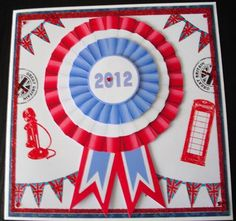 "Red White Blue Rosette on Craftsuprint designed by Liz Harrison - made by Lesley Earing - I printed out the design onto crafty Bobs premium gloss paper. I cut out all of the pieces and put to one side. I used an 8"" square blank white card as the base. Onto a square of bobs shiny paper I stamped bunting, telephone and ,telephone box then coloured them in with promarkers. I added some red glitter around the edges then matt and layered onto blue card which was then attached to the card blank…"