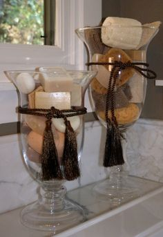 Vases filled with beautiful bath soaps and sponges – like how they vary in height and are finished off with silky dark brown ropes and tassels. Nice idea for containers to hold mini soaps and shampoos for guests/guest bathroom. Bathroom Towels, Small Bathroom, Master Bathroom, Bathroom Ideas, Bathroom Storage, Bathroom Staging, Brown Bathroom Decor, Tuscan Bathroom Decor, Bathroom Jars