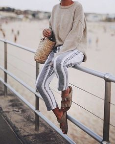 striped linen pants lightweight cream sweater woven bag and birkenstocks - perfect outfit for a chilly day at the beach for spring break - women's spring outfit inspiration