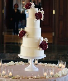 Five-tiered cake decorated with dark red and white flowers