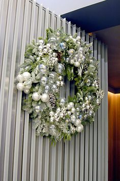 A full holiday wreath is embellished with chic white Christmas balls and pinecones painted silver.