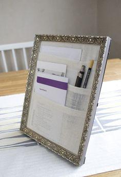 Mit einem Bilderrahmen und etwas Stoff können Broschüren, Unterlagen und Stifte verwahrt werden