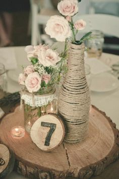 Dainty pink flowers and lace & bottles wrapped with twine on a slice of wood. Rustic chic table decor
