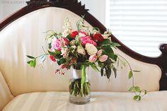 loose unstructured bridal bouquet of coral charm peonies, red ranunculus, Vendala roses, hot pink ranunculus, light pink lisianthus, jasmine vine, lemon leaf, peach stock & seeded eucalyptus wrapped in cream muslin ribbon