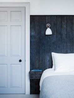 Dark Headboard made of board is painted deep blue and extends beyond bedside tables. Note light allows for hole free walls by running cords behind headboard