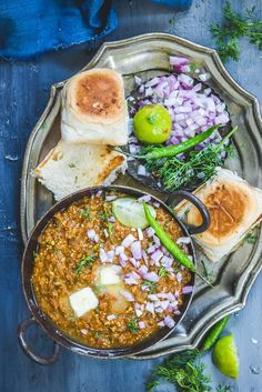Pav Bhaji served ina serving bowl along with onion and lemon.