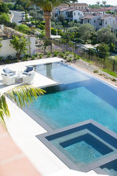 A white coffee table surrounded by white wicker chairs sits at a rectangular infinity pool finished with a spa. Luxury Swimming Pools, Dream Pools, Swimming Pools Backyard, Pool Spa, Swimming Pool Designs, Backyard Pool And Spa, Gunite Swimming Pool, Swimming Pool Tiles, Luxury Pools