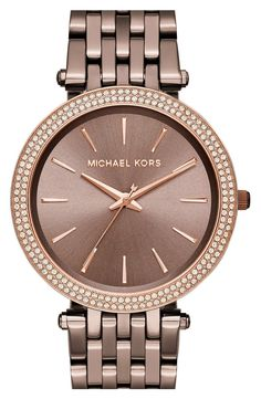 Bright crystals illuminate the sleek bezel of this elegant multi-link bracelet watch designed with a slender silhouette.