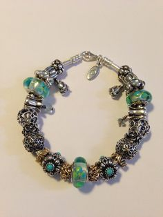 My clear teal flowers Murano glass charms and flower Pandora bracelet by Nicole.