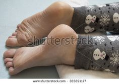 Beautiful feet of a woman are waiting for massage on a white towel on blue background. Woman wears grey winter leggings with snowflakes and snowman on it.