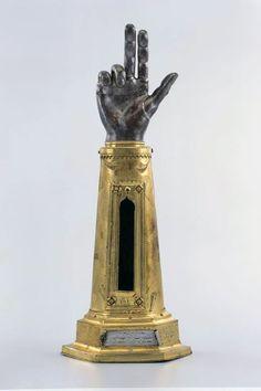 Armreliquiar  In Form eines menschlichen Armes mit durchgestreckten Schwörfingern. Inhalt: Ursus, hl. Datiert nach Inschrift 1474. Herkunft: Oberdorf. 46 x 18,2 x 12,5 cm. 1118,2 g. Kupfer, vergoldet.