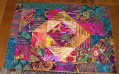 kaffe fassett fabrics - 6 1/2 inch squares put together and sew 1/4 inch seam down either side a line drawn from corner to corner. Bordered with 3 1/2 inch scraps.