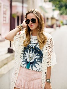 Julia Engel of Gal Meets Glam wearing a graphic t-shirt under an open-knit cardigan with statement jewelry