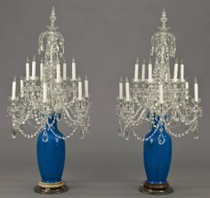 Pair of Impressive continental 12 light girandoles, the top formed with a cut glass baluster form support issuing two tiers of six scrolled arms joined with crystal swags and adorned with pendant drops, supported by a baluster form porcelain vase with a blue ground and incised floral decoration