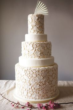 A hand-cut floral overlay with tiers of varying heights.Cake by Charm City Cakes