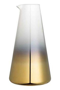 Jarra teñida: Jarra en vidrio teñido con forma de cono y pico. Diámetro superior 5 cm. Alto 23 cm.
