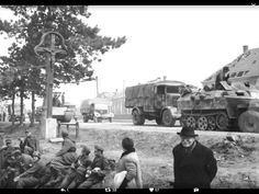Soldiers relaxing as a column of vehicles, including a Panther Ausf G tank, various supply trucks and a SdKfz 251/1 halftrack, passes by.