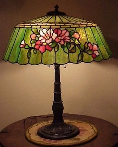 """Stunning example of Duffner  Kimberly. Double floral deign on opposite sides.  20 1/2"""" diameter; lamp stands just over 25"""" tall.  The characteristic Duffner  Kimberly leaf and berry motif base has its original Weber labeled sockets with their original porcelain lined interiors and satellite ended pull chains. Wired with period style cloth braided cord and an old plug.  Paul Crist's book """"Mosaic Shades II"""" shows this shade on a simpler base on p. 215."""