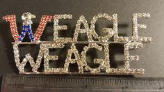 """""""Weagle Weagle War Damn Eagle"""" -- Cheer on the Auburn Tigers wearing one of these Weagle Weagle Rhinestone Pins. Rhinestones are clear with a red & blue W in a silver tone setting. Pins are 4"""" wide x 2 """" tall and have a pin back. Perfect for fundraising, for Sorority Sisters, for Loyal Fans. Pins are new in cellophane. Ships from Illinois. 18 pins available. Email tammy@blessingsandbling.com for purchase info."""