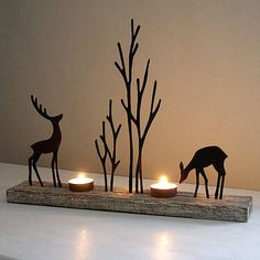 Tea light holder for cosy seasonal lighting. Reindeer woodland silhouette christmas decoration. Elegant and unusual tea light holder with rusty brown metal reindeers on a distressed whitewashed wooden base that suits contemporary or traditional settings. Creates lovely reflections once lit. Perfect size for on mantle pieces or as a dining table accessory making it a treasured decoration every year. Tea lights not included.Metal and wood28cm H 40cm L 7cm D