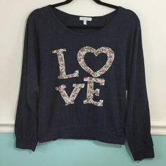 Delias long sleeved t-shirt top in navy LOVE Delias top in navy t-shirt type fabric. Long sleeved with banded waist. LOVE print on front in distressed floral pattern. No peeling. Shirt has been worn and washed a few times. Lots of wear left. Good condition no rips, stains or tears. Size Medium. Delias Tops Tees - Long Sleeve
