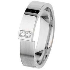 L'alliance PITCHAL est en or blanc et diamants. L'alliance est constituée d'un large anneau plat, l'or est d'un coté poli, d'un côté brossé. L'anneau est refermé en décalage et il est serti de 2 diamants qualité Hsi, poids total 0,034 carats. Une alliance sobre et moderne. [776,00€]