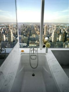 Bathroom with a view.  Something tells me, I would actually want to get out of bed to shower here.  Love the use of mirror to the left to expand the view further.  Genius!