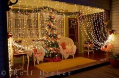 This brilliant display of Christmas lights turns a front porch into a magical cozy Christmas setting.  the impression of curtains as two comfy chairs sit between a nicely decorated tree. holidays