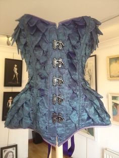 Hand dyed silk with organza scales. Silk lined. This can be made available in a choice of colours as the silk is custom dyed. Wide steel busk front opening with black metal hook closure. Modesty panel and satin ribbon laced eyelets at the back. In this sample created for an exhibition, I exposed the metal work that goes into a corset by encasing the metal bones in organza. For normal wear the metal boning would not be visible in this way.  Matching fabric based accessories can be made…