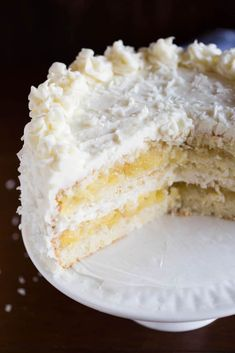 A sliced coconut cake with pineapple filling sitting on top of a white cake platter.