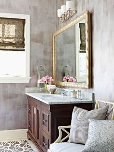 Dove Gray + Gold  Metallic gray walls create a dramatic backdrop in this regal master bathroom. Here, the luxurious Carrara marble countertop on the walnut vanity base mirrors the soothing gray on the walls. The shimmering gold mirror frame above the vanity subtly bounces light from the nearby window, echoing the room's gleaming chrome fixtures.