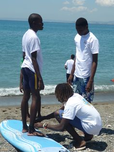 Preparing to hit the waves- Local Jamaican surfers at the the Surfing for Autism event prepare their board for a run. The event aimed at increasing autism awareness by teaching children how to surf. The day was sponsored by the Digicel Foundation amongst other local corporate sponsors