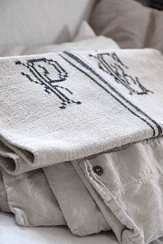 old flour sacks of coarse linen, hand embroidered with large monogram in cross stitch.