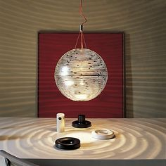 """The Terzani Magdalena Suspension Lamp, is a bold statement of Star Wars proportions. The light weight, tinted metal globe lets luminosity escape through its intricate configuration and cast amazing patterns on interior walls. The lamp consists of two hemispheres that clamp together. Guaranteed to garner attention in any environment. The Magdalena Large Suspension features a Terzani """"signature"""" red cord. The cord"""