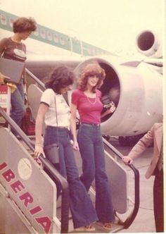 women's 1970s fashion. bell bottom means and fitted t-shirts