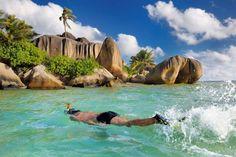 Man snorkelling at the famous beach of Anse Source d'Argent, La Digue, Seychelles.