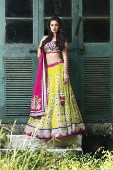 Net ghagra with contrast raw silk blouse, embellished with zardosi, and lumpy work along with net dupatta.