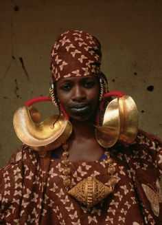 Africa | A Peul woman wears large gold earrings. She also has her lips tattooed in the traditional style. Mali