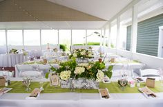 Tables were decorated in crisp white linens and chartreuse burlap runners.   Venue/Caterer: Benton Grove Bed & Banquets  Floral Designer: Blooms Florist