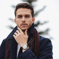 A navy blue top coat/pea coat With a red scarf. Really elegant appearence.  Model: Adam Gallagher.