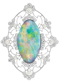 Edwardian Platinum, Black Opal, Diamond and Pearl Brooch. Centring one oval opal approximately 14.75 cts., within a pierced openwork frame of floral motif, set with 8 seed pearls and 42 small old European-cut and single-cut diamonds, circa 1910. #Edwardian #brooch