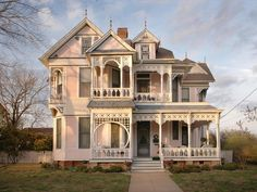 This detailed exterior is an authentic example of the gingerbread-style Victorian. Delicate architectural detail and a multi-gabled roofline are characteristic of the style and era. White molding decorates the front porch and multiple balconies, providing subtle contrast to the pale pink exterior for added visual interest.