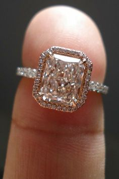 Pink diamond radiant cut engagement ring: This is a real showstopper, and it's the kind of engagement ring that takes everyone's breath away. The central stone is beautifully outlined in a halo that artfully mirrors the radiant cut of the diamond, while the rose gold hue of the setting further warms up its color.   Halo Engagement Rings for a Sparkling New Year